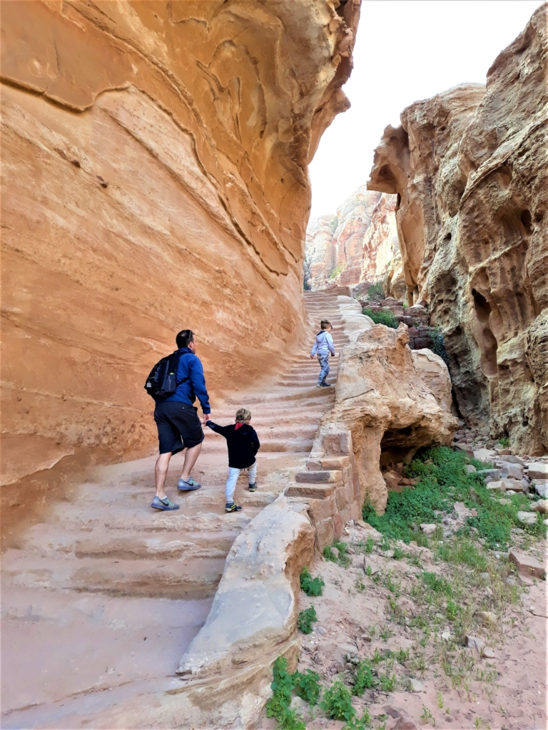 kids climbing up steps on their visit to Petra to the High Place of Sacrifice
