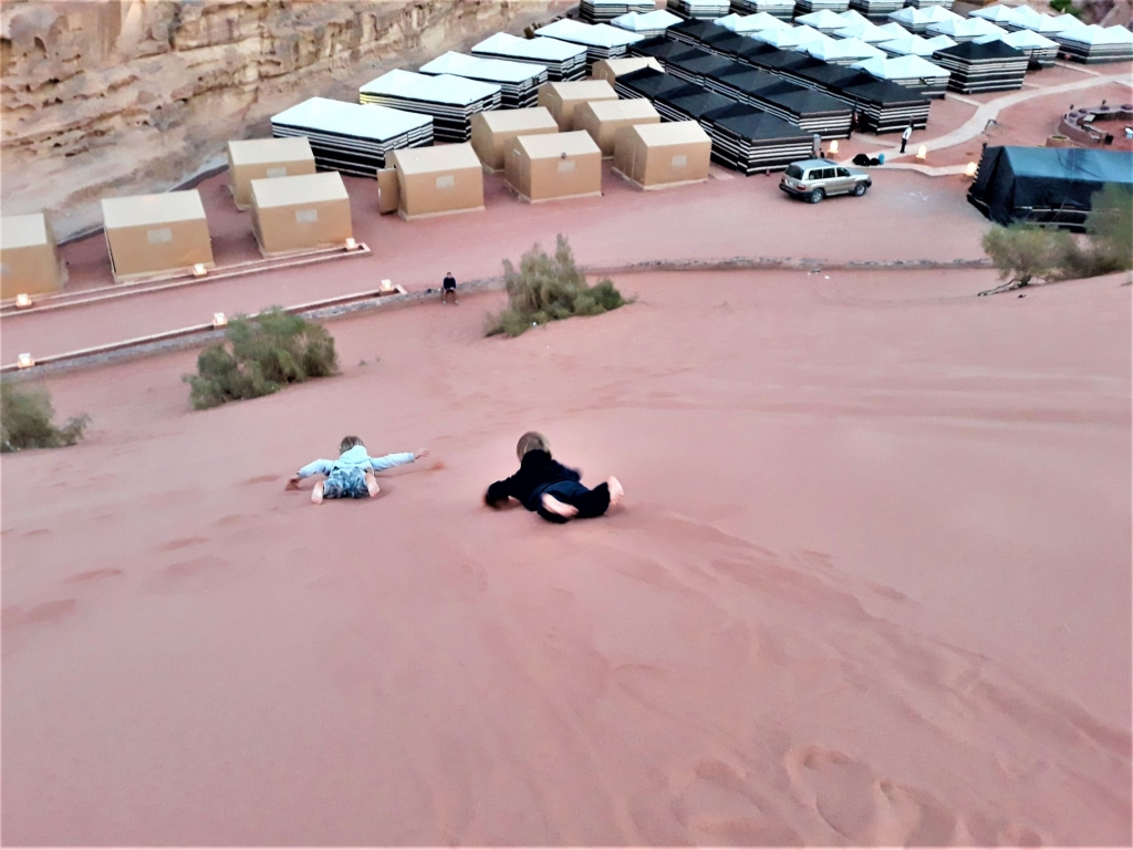 Visiting Jordan with kids: body suring down the sand dunes in Wadi Rum