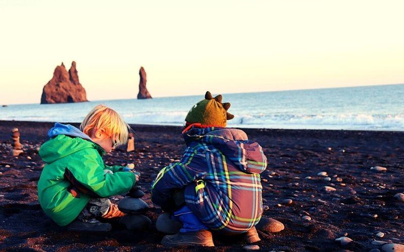 Kids enjoying the novelty of a black sand beach
