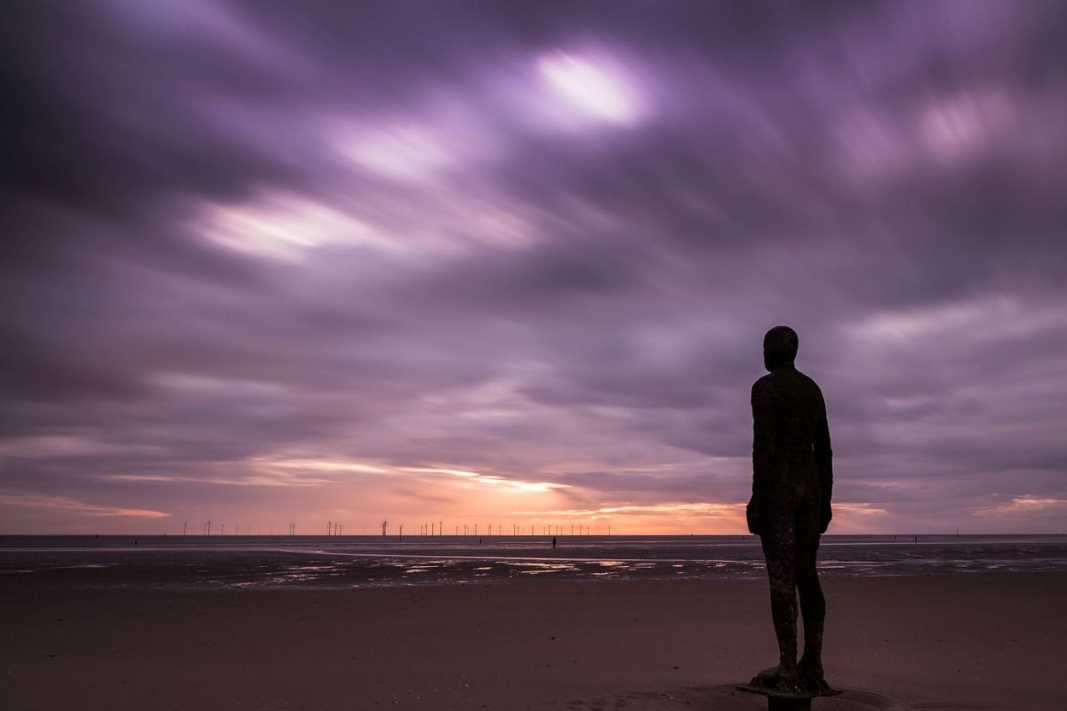 Antony Gormley Another Time statue at low tide.