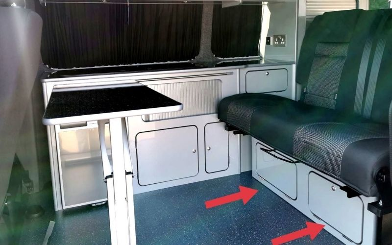 Cupboards under the back seats in a VW campervan.
