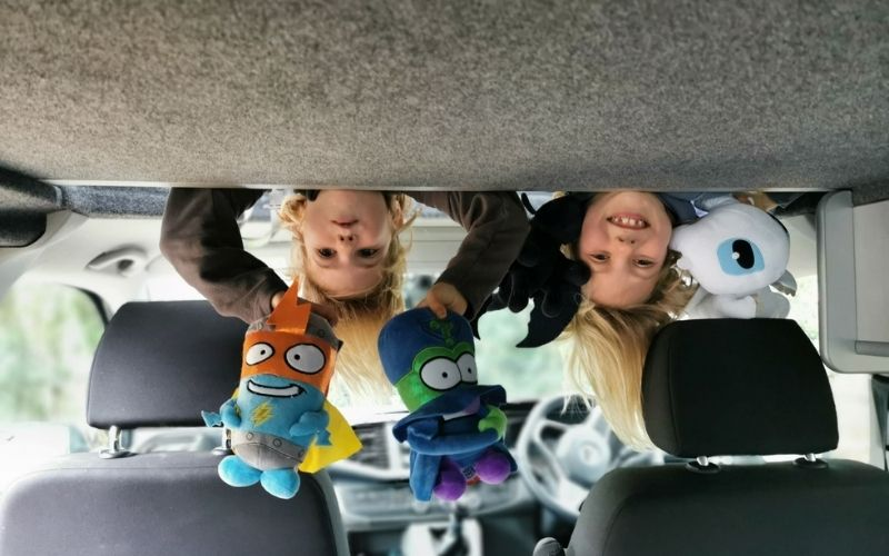 Kids playing in the pop top roof in a campervan.