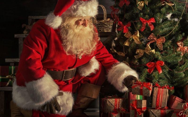 Santa placing presents under the Christmas tree.