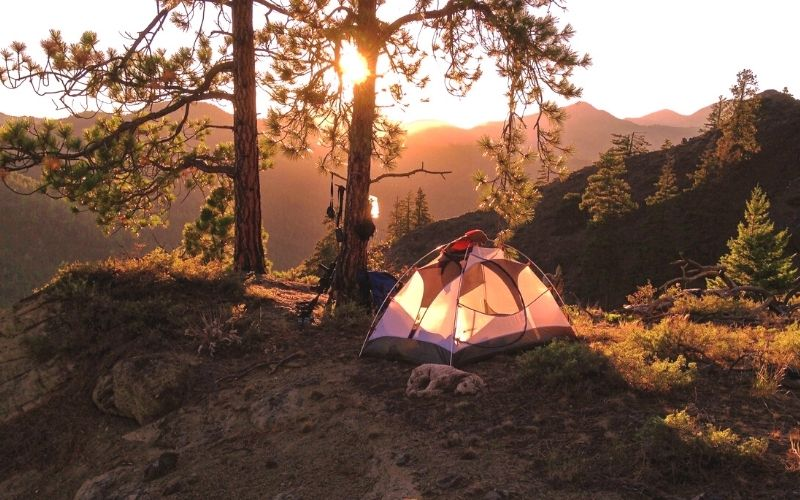 Sun rising over the mountains with tent in foreground