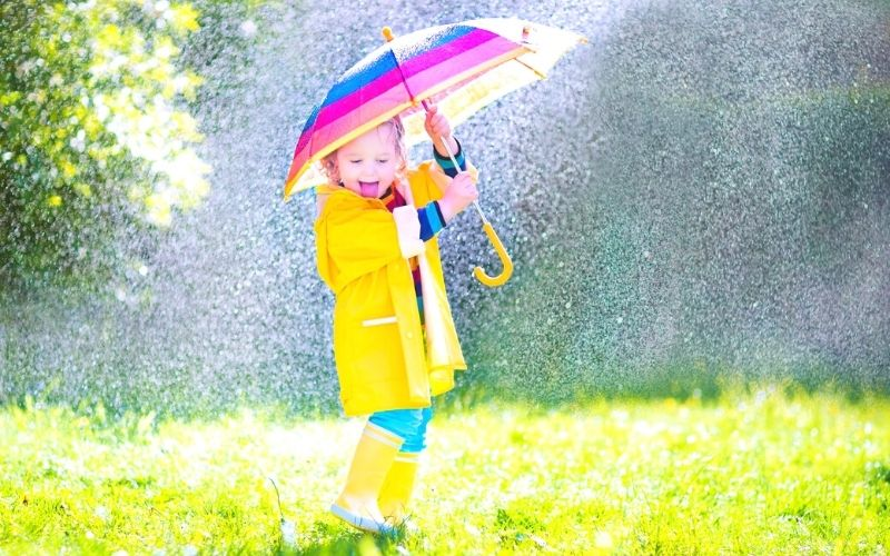 Toddler playing with a colourful umbrella in the rain.