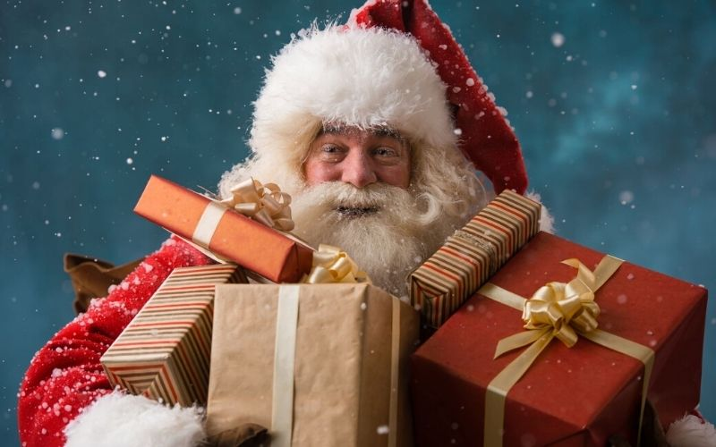 Father Christmas carrying Christmas presents.
