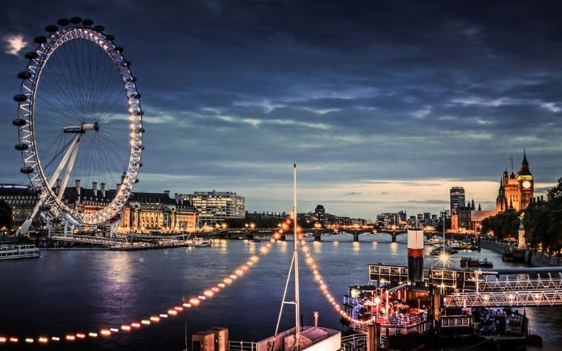 London Eye at twilight with lights of the London skyline.