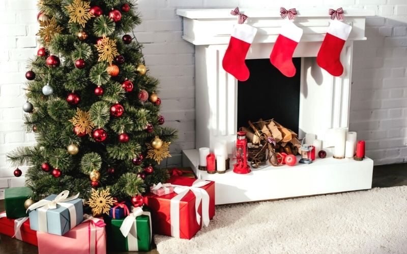 Christmas tree with presents and stockings hanging from fireplace.