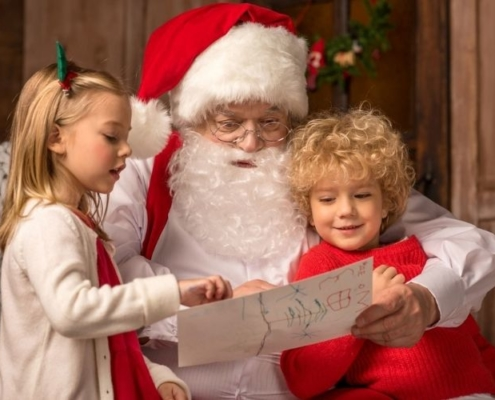 Santa reading to children at Santa sleepovers and Christmas at theme parks